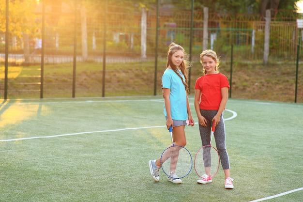 Dwie dziewczyny z rakietami do badmintona na boisku.