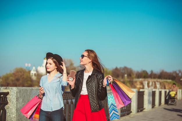 Dwie dziewczyny z torby na zakupy na ulicach miasta w słoneczny dzień