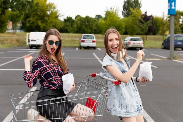 Dwie dziewczyny zabawy na parkingu w supermarkecie.