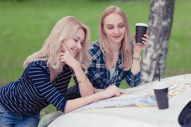Dwie dziewczyny zatrzymały się na drodze, aby uzyskać wskazówki i napić się kawy