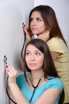 Dwie dziewczyny ze stetoskopami słuchają ściany.