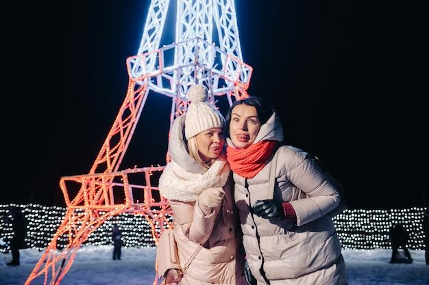 Dwie dziewczyny zimą z palącymi się sylwestrowymi światłami na świątecznej ulicy