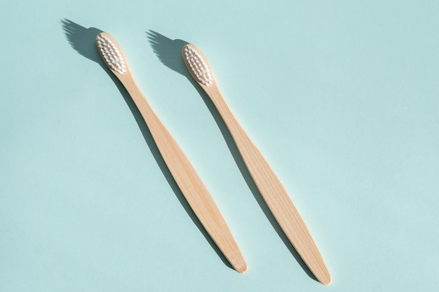Dwie ekologiczne bambusowe drewniane szczoteczki do zębów na jasnoniebieskim tle mocne światło widok z góry