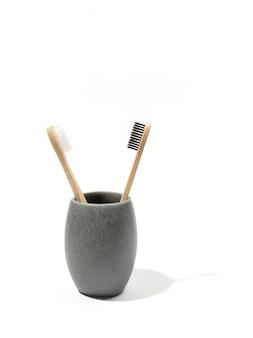 Dwie ekologiczne drewniane bambusowe szczoteczki do zębów w szarym kamiennym kubku na białym tle. koncepcja ekologicznych produktów zero waste, bez plastiku, koncepcja zrównoważonego stylu życia. skopiuj miejsce.