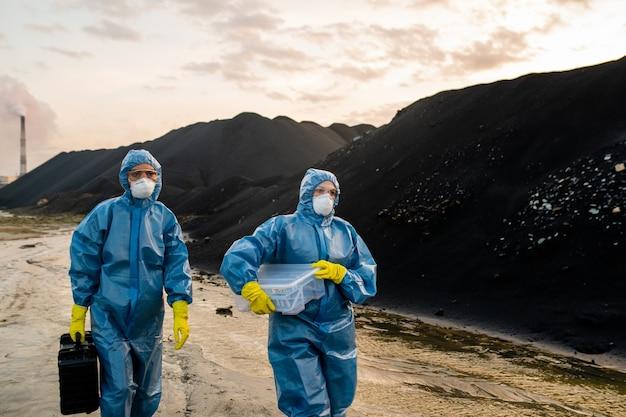 Dwie ekologki w konalach, respiratorach, okularach i gumowych rękawiczkach niosące walizki z próbkami gleby podczas poruszania się po drodze