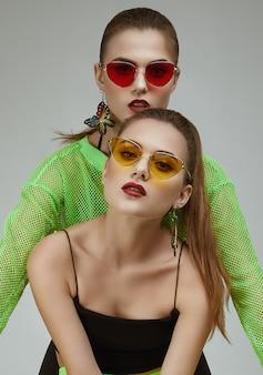 Dwie eleganckie glamour hipster bliźniaczki w modnych neonowych zielonych sukienkach