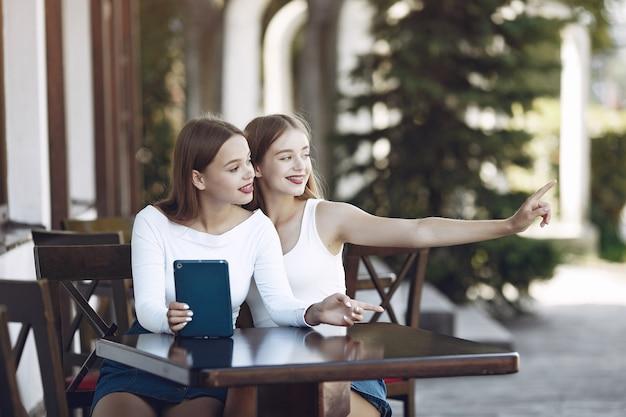 Dwie eleganckie i stylowe dziewczyny w letniej kawiarni