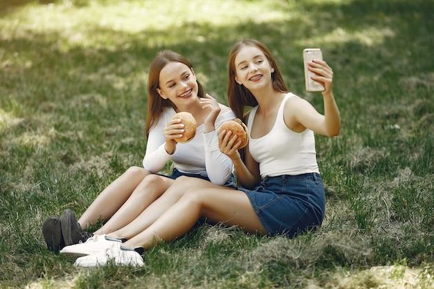Dwie eleganckie i stylowe dziewczyny w wiosennym parku