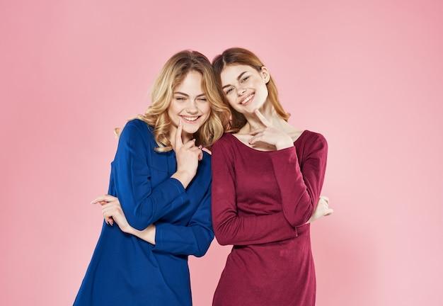 Dwie eleganckie kobiety w sukniach mody dziewczyna luksus różowym tle