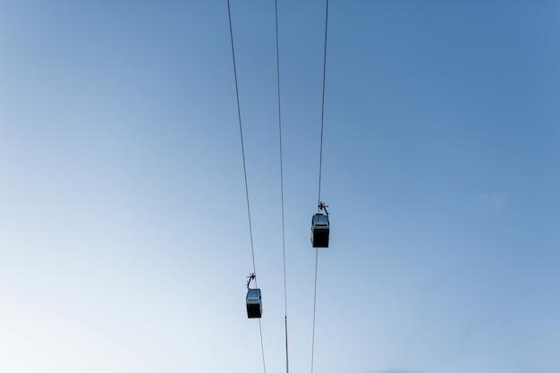 Dwie elektryczne kolejki linowe na tle błękitnego jasnego nieba. ośrodek wczasowy. aktywny wypoczynek ekstremalny. widok z dołu.