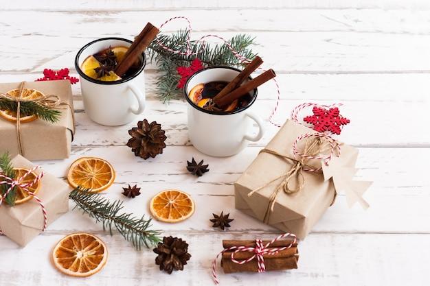 Dwie emaliowane białe kubki z gorącym grzanym winem z przyprawami i pudełka na prezenty. kartkę z życzeniami na ferie zimowe.