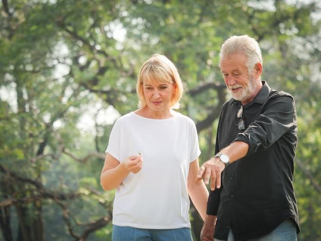 Dwie emerytury szczęśliwy seniorów mężczyzna i kobieta idą i rozmawiają w parku
