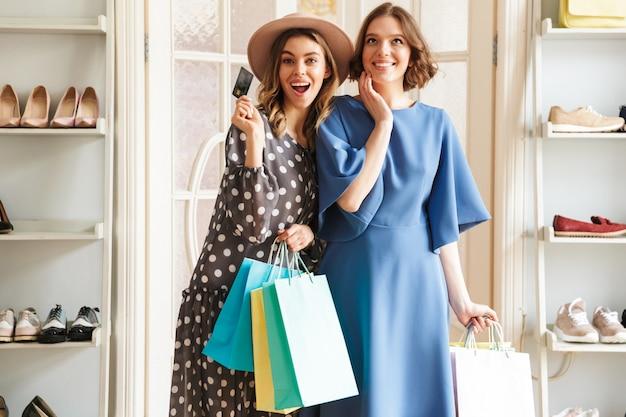 Dwie emocjonalne młode kobiety shopaholics z torby na zakupy i karty kredytowej.