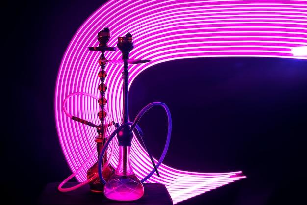 Dwie fajki wodne z węglami shishy z różowym neonowym oświetleniem na ciemnym tle