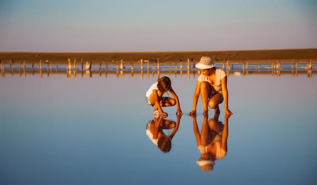 Dwie fantastycznie piękne dziewczyny w niezwykłych strojach na pięknym przezroczystym słonym jeziorze szukają czegoś w błyszczącej tafli