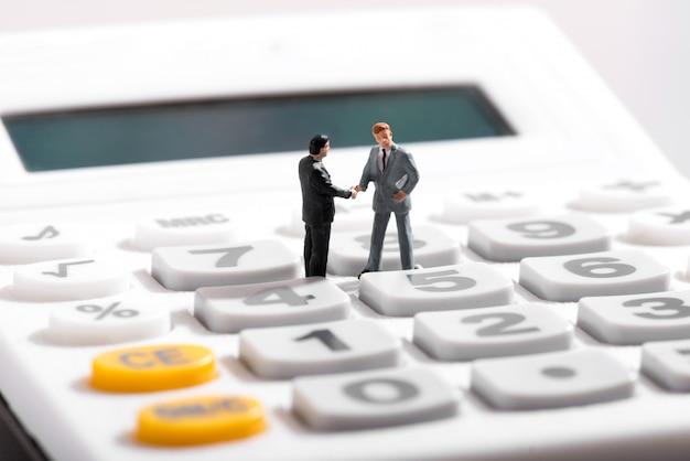 Dwie figurki stojące na kalkulatorze