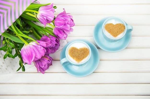 Dwie filiżanki cappuccino z symbolem w kształcie serca i fioletowymi tulipanami na drewnianym tle