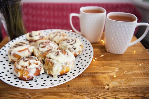 Dwie filiżanki czarnej herbaty stoją na drewnianej tacy, bukiet suszonej lawendy. świeże i pachnące bułeczki cynamonowe z bliska leżą na talerzu z kropkami, piękny poranek.