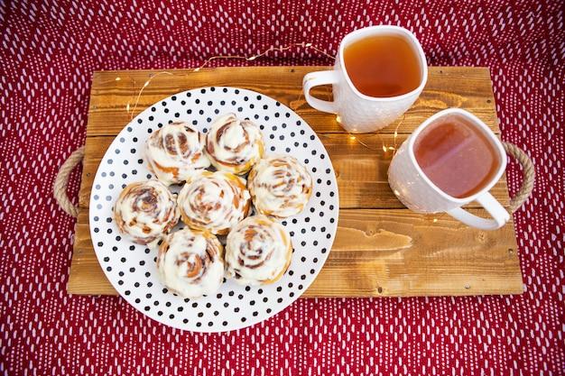 Dwie filiżanki czarnej herbaty stoją na drewnianej tacy. świeże i pachnące bułeczki cynamonowe z bliska leżą na talerzu z kropkami, piękny poranek. zbliżenie. romantyczny poranek.
