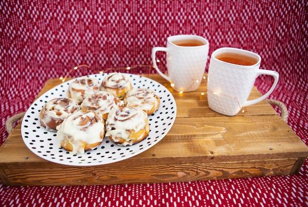Dwie filiżanki czarnej herbaty stoją na drewnianej tacy. świeże i pachnące bułeczki cynamonowe z bliska leżą na talerzu z kropkami, piękny poranek.
