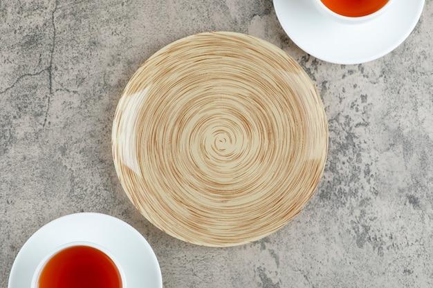 Dwie filiżanki czarnej herbaty z pustym talerzem na marmurze.