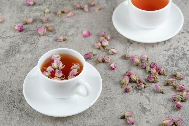 Dwie filiżanki czarnej herbaty z suszonymi kwiatami na marmurze.