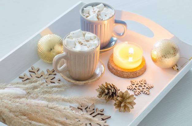 Dwie filiżanki gorącego napoju z piankami i świątecznym wystrojem na białej drewnianej tacy