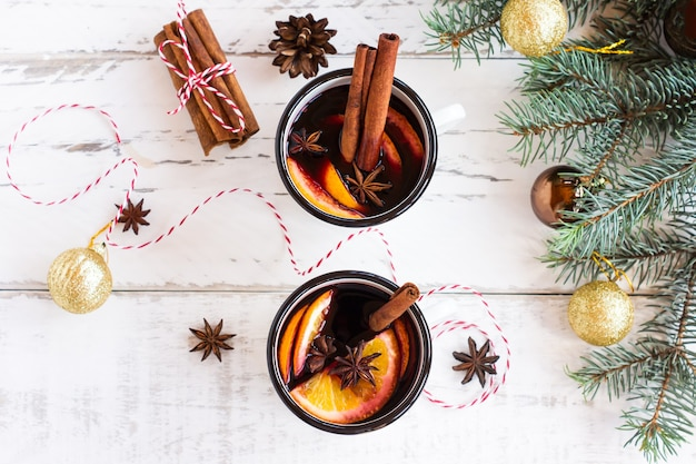 Dwie filiżanki grzanego wina jesienią lub gluhwein z przyprawami i plastrami pomarańczy na rustykalnym widoku z góry. tradycyjny napój na jesienne i zimowe wakacje.