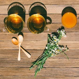 Dwie filiżanki herbaty, miodu, drewniane łyżki i bukiet stokrotek