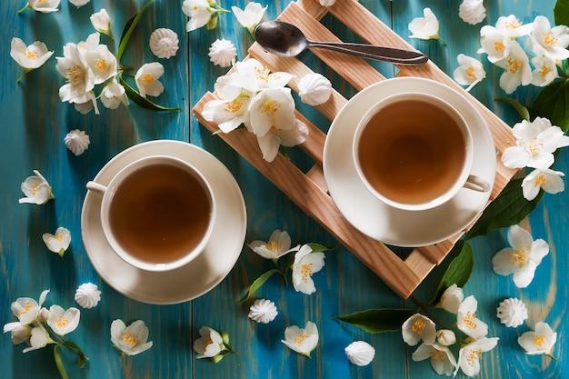 Dwie filiżanki herbaty na drewnianej mini palecie otoczonej kwiatami jaśminu. widok z góry
