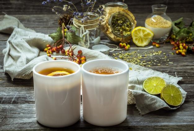 Dwie filiżanki herbaty na pięknym drewnianym tle z cytryną i ziołami, zima, jesień