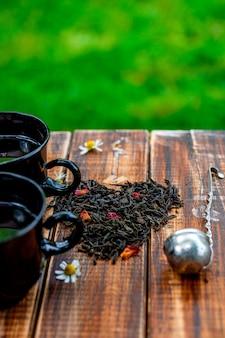 Dwie filiżanki herbaty w pobliżu suchych liści czarnej herbaty mają kształt serca