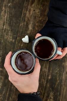 Dwie filiżanki herbaty w przyrodzie w rękach para w czarnych rękawiczkach na powierzchni drewnianych