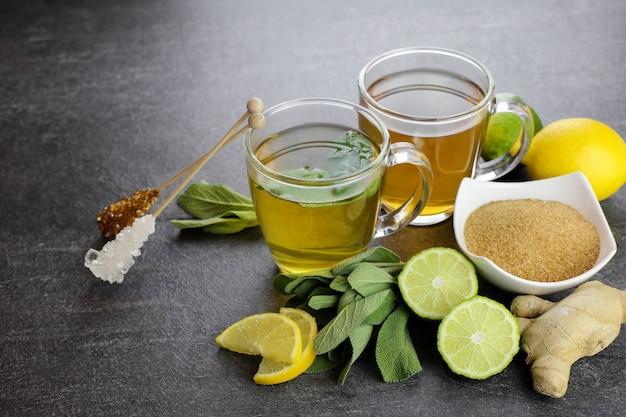 Dwie filiżanki herbaty ziołowej w szklanych filiżankach z szałwią, imbirem, cytryną i limonką, cukier brązowy i paluszki cukrowe na ciemnym tle