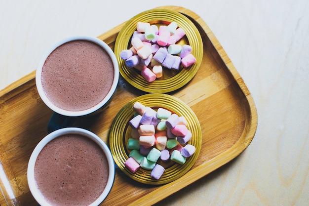 Dwie filiżanki kakao z różnokolorową pianką na złotych spodkach.
