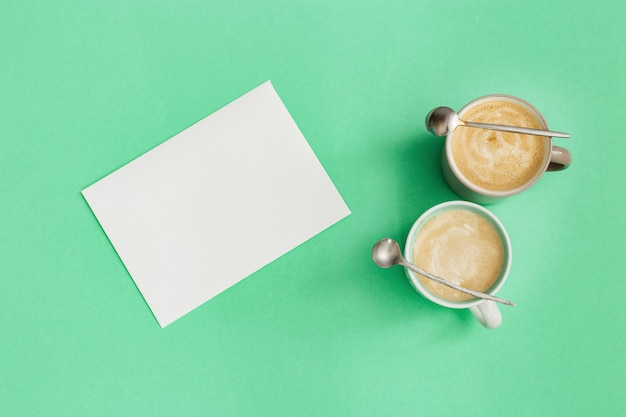 Dwie filiżanki kawy cappuccino, mała łyżka i czysty papier do pisania pomysłów. czas na odpoczynek i refleksję. widok z góry i płaskie leżały na tle mięty w kolorze trendu.