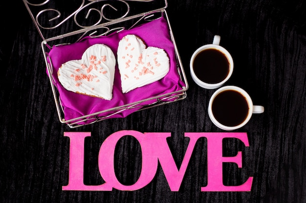 Dwie filiżanki kawy, ciasteczka w formie serca napis miłość z bliska