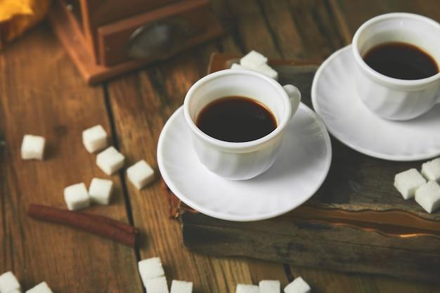 Dwie filiżanki kawy espresso w pobliżu kostek cukru
