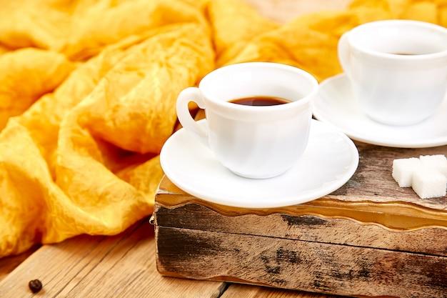 Dwie filiżanki kawy espresso w pobliżu kostki cukru