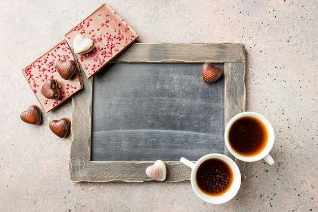 Dwie filiżanki kawy i cukierki czekoladowe w kształcie serca na tle tablicy na walentynki koncepcja. widok z góry