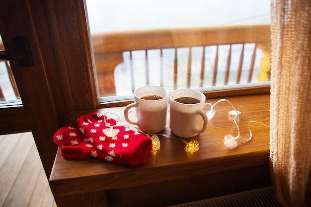 Dwie filiżanki kawy i czerwone mitenki leżą na parapecie w drewnianym domu w karpatach