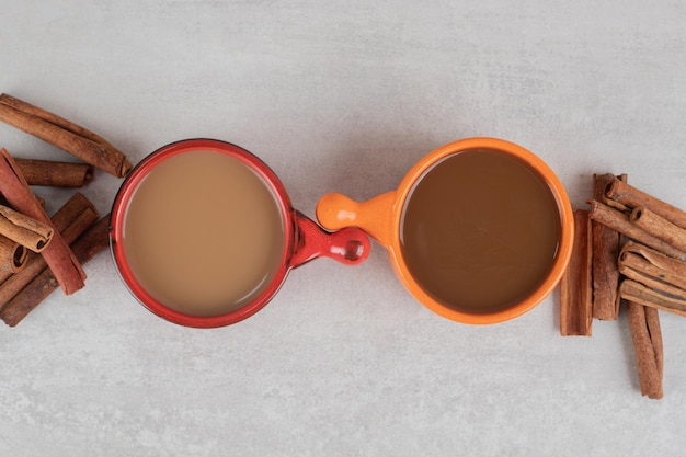 Dwie filiżanki kawy i laski cynamonu na marmurowej powierzchni