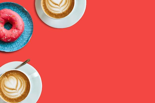 Dwie filiżanki kawy i pączki
