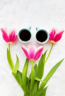 Dwie filiżanki kawy i trzy piękne różowe tulipany