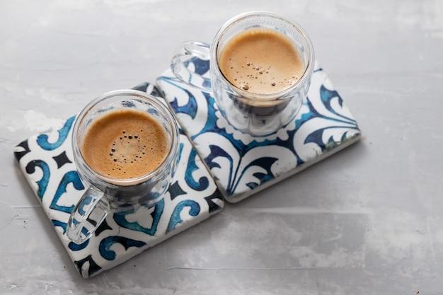 Dwie filiżanki kawy na ceramicznym tle