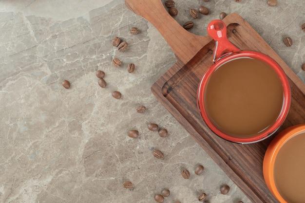 Dwie filiżanki kawy na drewnianej desce z ziarnami kawy