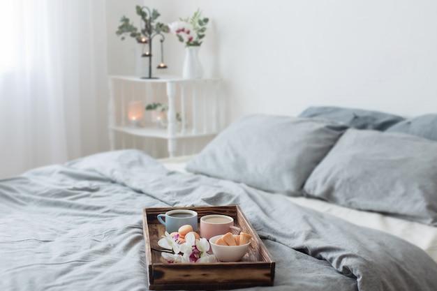 Dwie filiżanki kawy na drewnianej tacy w sypialni