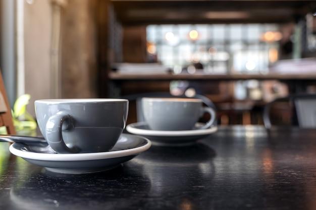 Dwie filiżanki kawy na drewnianym stole w kawiarni