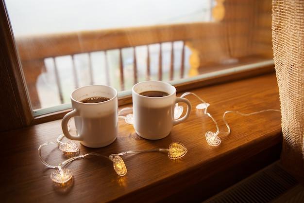 Dwie filiżanki kawy na parapecie w drewnianym domu w karpatach