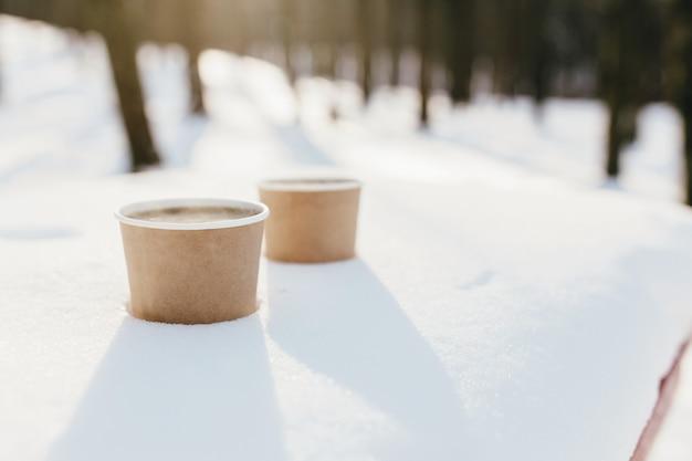 Dwie filiżanki kawy na śniegu w lesie